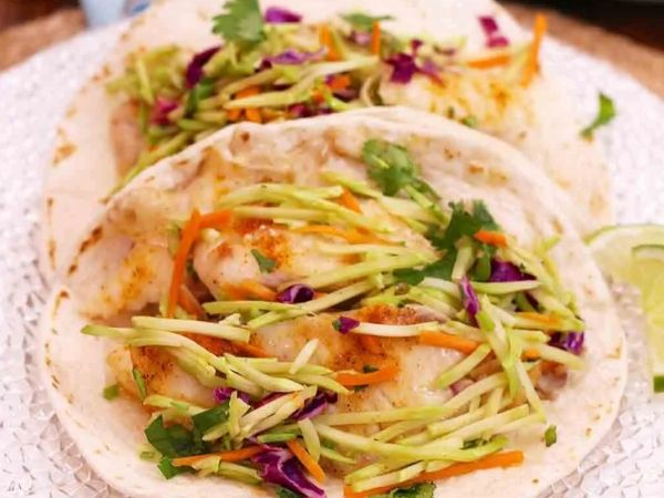 photo shows a fish taco with broccoli slaw