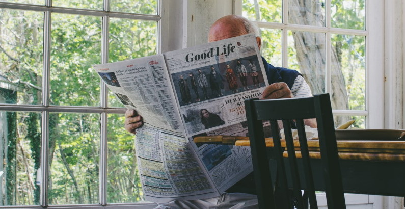 photo of a senior man at home reading newspaper