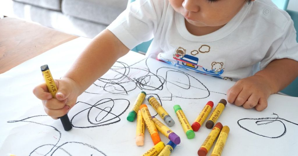 photo of kid scribbling with crayon on paper