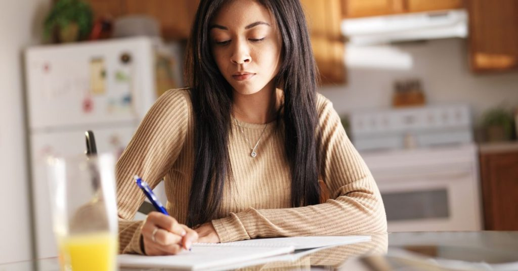 photo of a girl studying at the dining table at home