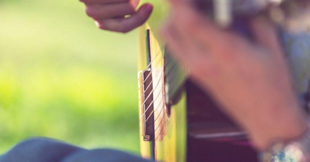 photo a guitar being strummed up close